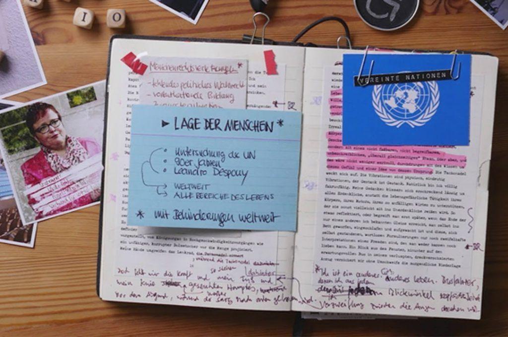"""Filmstill aus """"Inklusion - eine Spurensuche"""": Ein aufgeklapptes Buch mit Notizen und einer beschrifteten Karteikarte."""