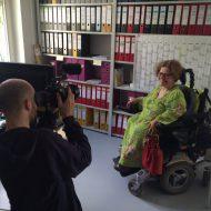 In einem Büro wird eine Frau im Elektro-Rollstuhl gefilmt.