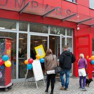 Vor einem knallroten Neubau stehen Menschen unterschiedlichen Alters. Über der Tür steht in großen Lettern KOMPASS. Am Eingang sind Luftballons angebracht.