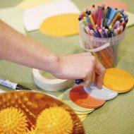 Ein Tisch mit bunten Karten, Klebeband und einem kleinen Eimer voll mit Filzstiften. Im Vordergrund gelbe Massagebälle.