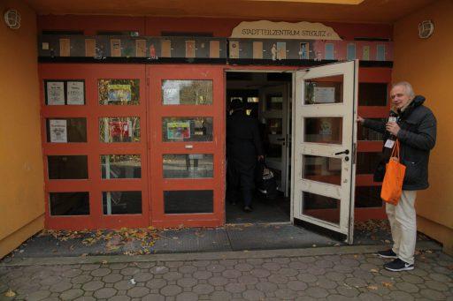 """Ein Mann mittleren Alters hält die Tür zu einem Gebäude auf. Über der Tür steht auf einem Schild """"Stadtteilzentrum Steglitz""""."""