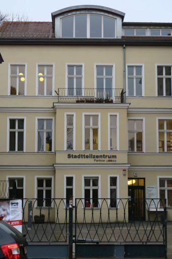 """Die Frontansicht eines Altbaus mit gelber Fassade und hohen Fenstern. Auf Höhe der ersten Etage prangt der Schriftzug: """"Stadtteilzentrum Pankow"""""""