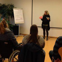 Eine Seminarsituation: Eine Frau mit langen blonden Locken neben einem Flipchart. Vor ihr sitzen rund 10 Menschen im Halbkreis.