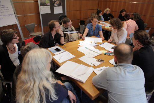 Mehrere Tischgruppen mit diskutierenden Menschen