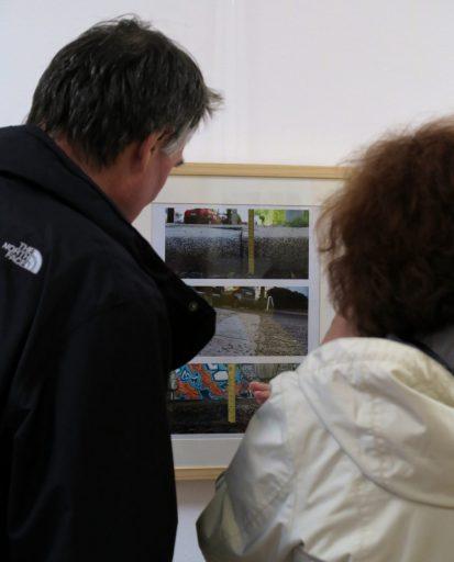 Zwei BesucherInnen einer Ausstellung betrachten ein gerahmtes Bild mit zwei Fotos. Die Fotografien zeigen Bordsteine, die entweder abgesenkt sind oder deren Höhe mithilfe eines gelben Maßbandes oder Zollstocks gemessen wird.