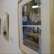 Eine Wand mit gerahmten Fotos. Im Vordergrund ein Bild bestehend aus zwei Fotografien, auf denen Baustellen abgebildet sind. Die Absperrungen der Baustellen sind unterschiedlich gut markiert.