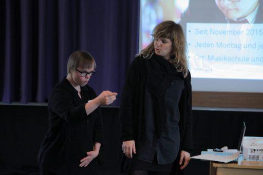 Eine Frau mit Down-Syndrom hält einen Vortrag. Neben ihr steht eine andere Frau und blickt sie an.
