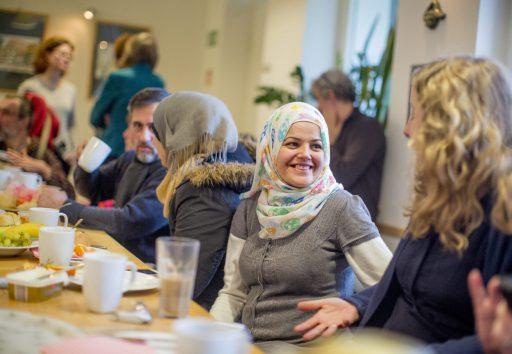 Zwei junge Frauen, die an einem großen Frühstückstisch sitzen und sich freudig unterhalten