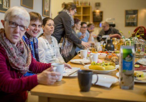 Viele Menschen an einem reichlich gedeckten Frühstückstisch