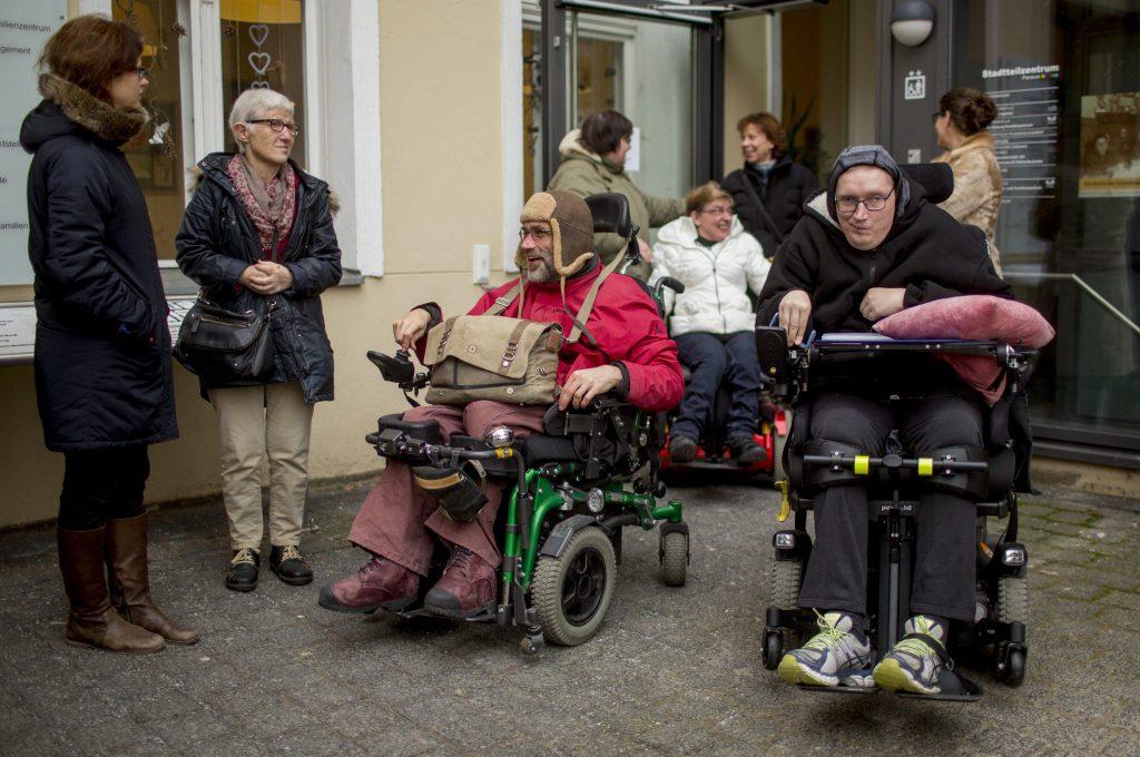 Menschen im Rollstuhl, die durch die Glastür eines Gebäudes auf einen gepflasterten Hof gelangen.