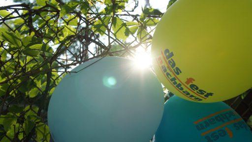 """Sonne scheint durch einen pflanzenbewachsenen Maschendrahtzaun. Daran angebracht 3 bunte Ballons mit der Aufschrift """"Fest der Nachbarn""""."""