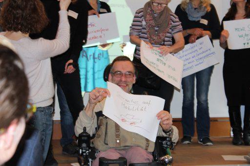 """Ein Mann im Rollstuhl hält strahlend ein Plakat hoch, auf dem steht: """"Garantie auf Mobilität"""". Um ihn herum mehrere andere Menschen mit Plakaten."""