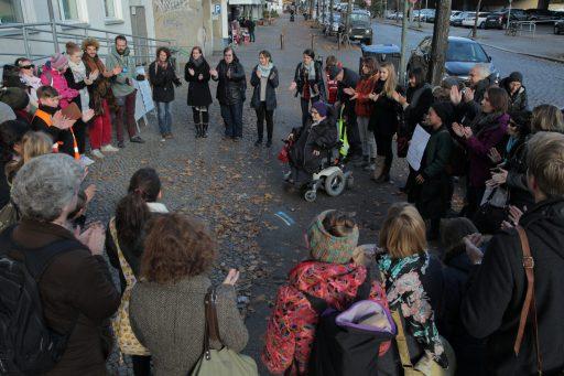 Auf einer Straße: Viele Menschen stehen in einem Kreis und klatschen. Etwas in der Mitte des Kreises eine Frau im Rollstuhl.