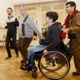 Mehrere Menschen, die sich an den Händen halten und im Kreis tanzen. Im Vordergrund eine junge Frau im Rollstuhl.