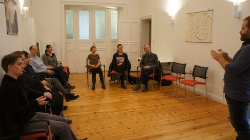 In einem großen Raum mit Dielenboden: Mehrere Menschen sitzen im Halbkreis und schauen aufmerksam auf einen Gebärdendozenten.