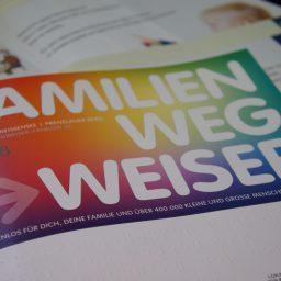 """Hefte mit dem Titel """"Familienwegweiser Pankow"""" übereinander liegend. Im Hintergrund aufgeschlagene Seiten in Leichter Sprache."""