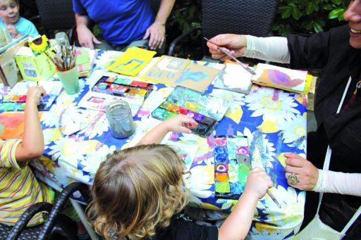 Kinder und Erwachsene sitzen um einen Tisch und malen mit Wasserfarben.