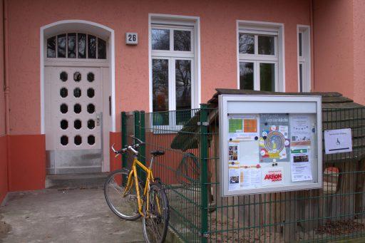 Die Tür eines Hauses mit rosafarbener Fassade. Zur Straße ein Aushangkasten mit Einladungsflyern.
