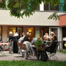 Auf der Terrasse eines Neubaus: Lebendiges Treiben vieler unterschiedlicher Menschen. Einige sitzen auf Holzstühlen um Tische herum.