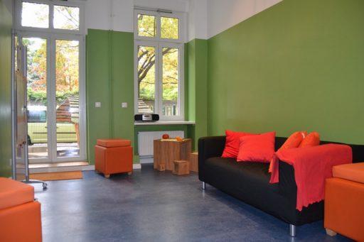 Ein halb in grün gestrichener Raum mit Terrassentür und bequemen Sitzmöbeln.