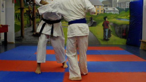 Die Unterkörper zweier Menschen, die auf einer rot-blauen Matte Kampfsport machen.
