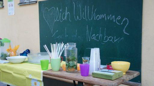 """Auf einer Tafel hinter einem Tisch mit sommerlichen Getränken steht mit Kreide geschrieben: """"Herzlich Willkommen beim Fest der Nachbarn"""""""