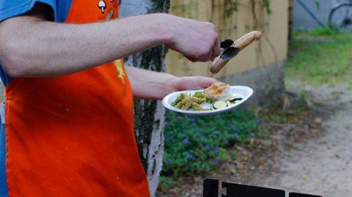Draußen: Ein Mann mit roter Schürze und einem Pappteller mit Salat in der linken Hand hält mit einer Zange eine Bratwurst.