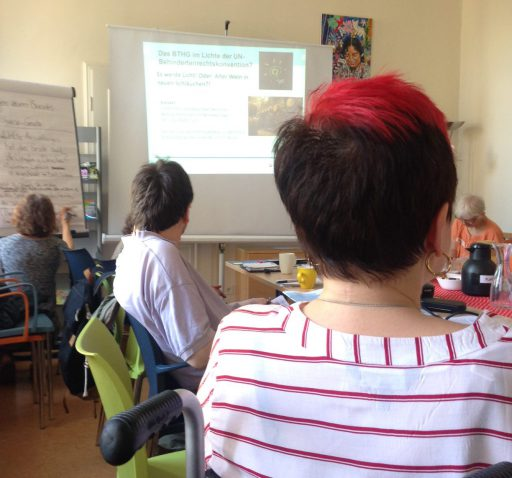 Eine Arbeitsgruppe mit mehreren Menschen. Im Vordergrund eine Frau mit kurzen rot-schwarz gefärbten Haaren. Hinten eine Leinwand, auf die eine Präsentation projiziert ist.