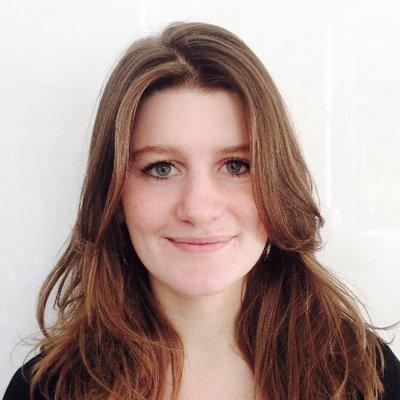 Eine junge Frau mit langem braunen Haar, freundlich lächelnd