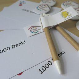 """Auf einem Tisch liegen Buttons, Stifte und Postkarten mit dem Logo von """"Stadt Inklusive!"""" und der Aufschrift """"1000 Dank"""""""