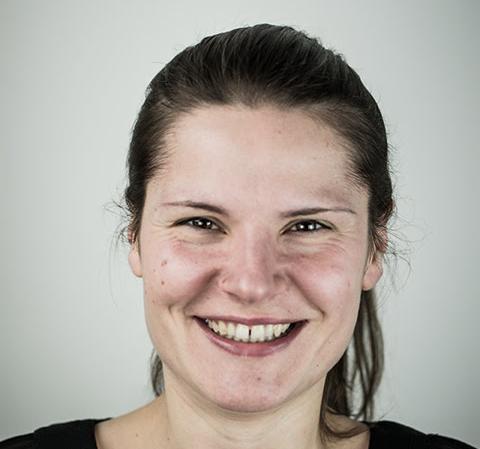 Eine junge Frau mit langem, zum Zopf gebundenen braunen Haar, freundlich lachend