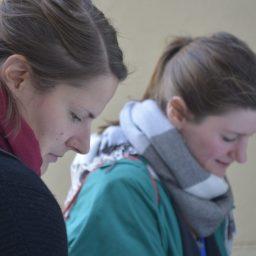 zwei junge Frauen mit langem, braunen Haar stehen nebeneinander und schauen nach unten