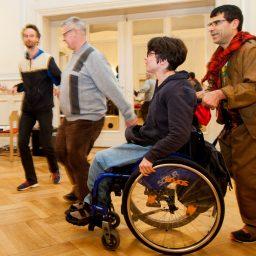 Männer und Frauen tanzen in einem großen Saal