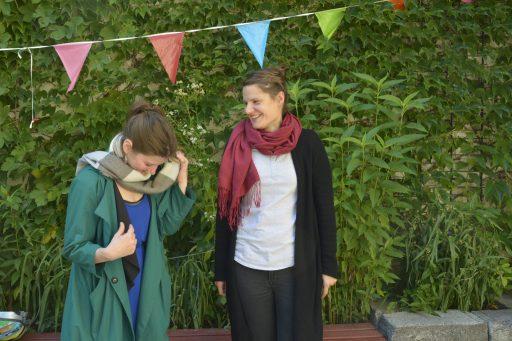 Zwei junge Frauen mit langen, braunen Hasrren, zum Zopf gebunden stehen nebeneinander vor einer Efeu_Wand. Beide lachen. Eine der Frauen schaut nach unten.