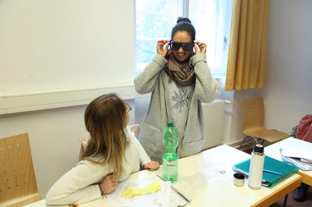 In einem Seminarraum: Eine junge, hinter einem Tisch stehende Frau setzt sich eine Simulationsbrille auf und lacht. Eine bei ihr sitzende Kommilitonin schaut zu ihr auf.