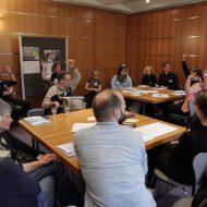 In einem Seminarraum verschiedene Menschen an Tischgruppen. Die meisten melden sich per Handzeichen.