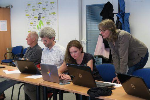 Eine Seminarsituation: Eine Dozentin steht hinter einer sitzenden Seminarteilnehmerin und erklärt ihr etwas an deren Laptop.