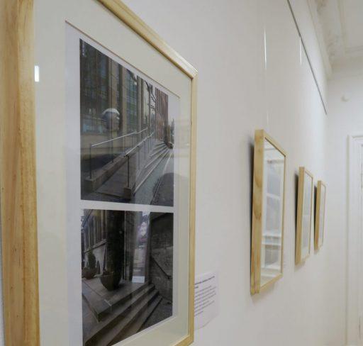 Vier in Holz gerahmte, hochformatige Bilder an einer weißen Wand. Gerahmt sind je zwei bzw. drei Fotografien. Rechts neben jedem Exponat ist ein Text angebracht.