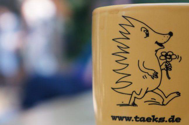 """Eine ockergelbe Tasse. Darauf eine Zeichnung eines Igels mit einer Blume in der Hand und dem Text """"www.taeks.de"""""""