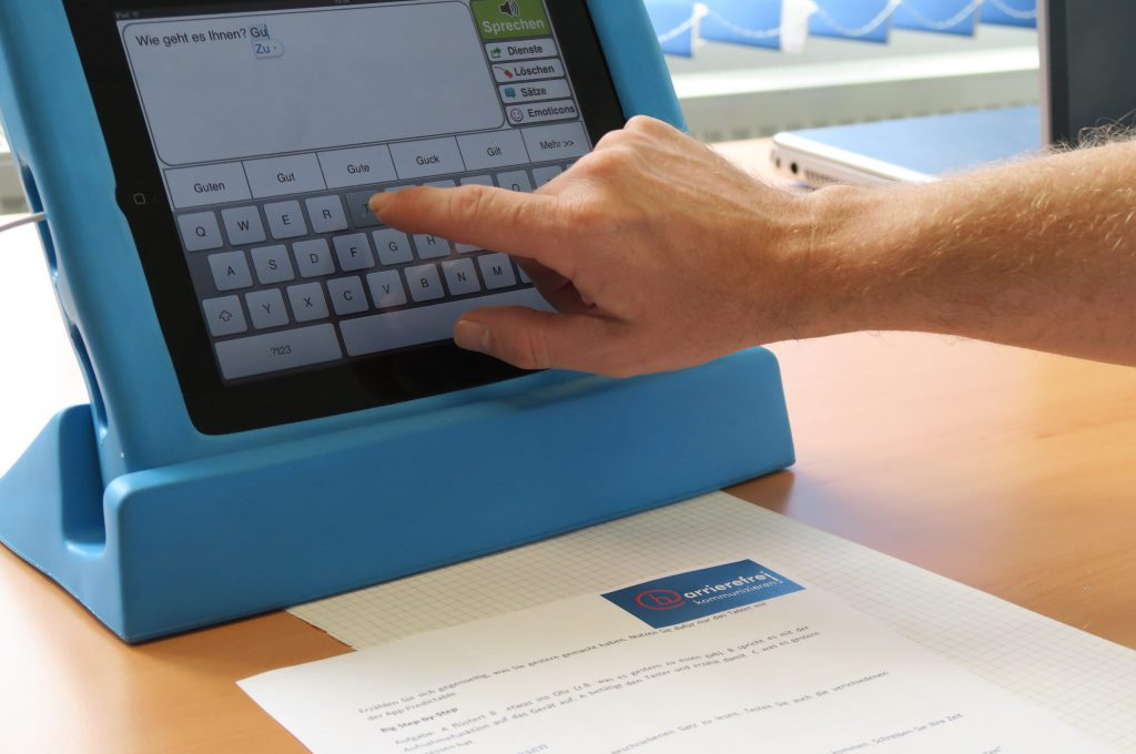 """Ein Tablet mit einer App zur Unterstützten Kommunikation. Eine Männerhand schreibt auf der eingeblendeten Tastatur. Zu lesen ist: """"Wie geht es Ihnen? Gu"""""""