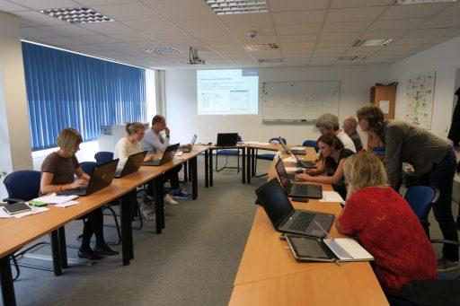 Ein Seminarraum. Menschen sitzen u-förmig an Tischen und arbeiten an Laptops.