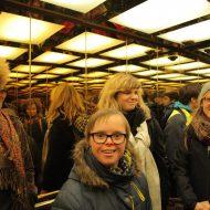 Mehrere junge Menschen in einem Fahrstuhl mit vielen Spiegeln.