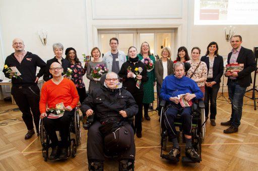 Gruppenfoto in einem Tanzsaal. In der vorderen Reihe einige Menschen im Rollstuhl.