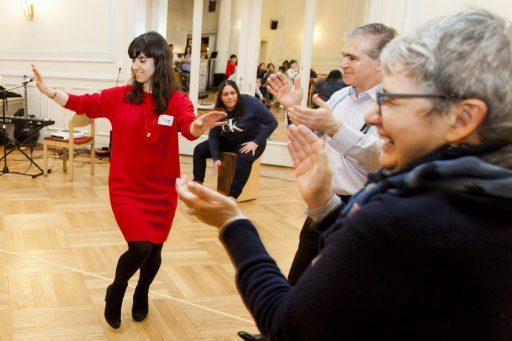In einem Tanzsaal: Eine Frau in rotem Kleid tanzt, die um sie herum stehenden Menschen klatschen.