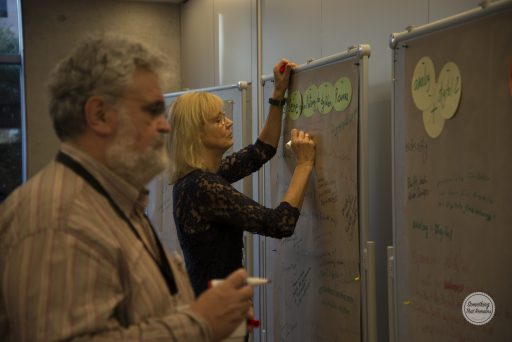 """Ein Mann und eine Frau machen Notizen auf Plakate, die an Stellwände angebracht sind. Es sind die Überschriften """"analog und digital"""" sowie """"Nutzung des digitalen Raumes"""" zu lesen."""