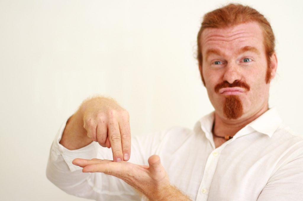 Rothaariger Mann in weißem Hemd, der mit beiden Händen eine Gebärde macht