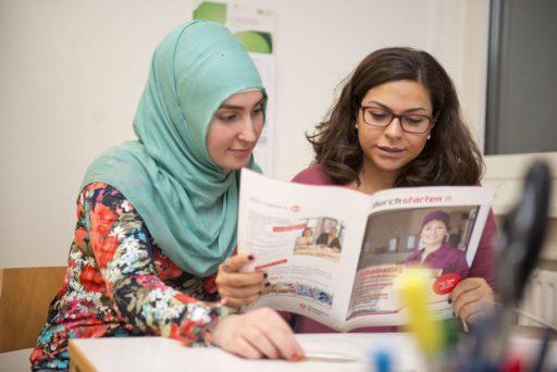 """Zwei Frauen, eine mit Kopftuch, lesen in einer Zeitschrift mit dem Titel """"durchstarten""""."""