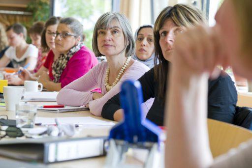 Mehrere Frauen unterschiedlichen Alters an einem Tisch mit Arbeitsmaterialien. Alle schauen aufmerksame in eine Richtung.