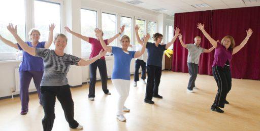 Mehrere Frauen unterschiedlichen Alters in einem Tanzraum. Sie tragen Sportkleidung und werfen lachend die Arme in die Höhe.