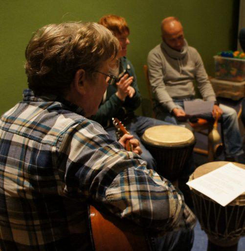 Ein Mann mit Gitarre von der Seite. Im Hintergrund zwei andere Musizierende. Vor ihnen stehen hohe Trommeln.